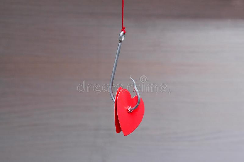 A metal fishing hook hanging on a rope pierced tow hearts of the red cardboard. Concept of love. Valentine`s day. And wedding stock photos