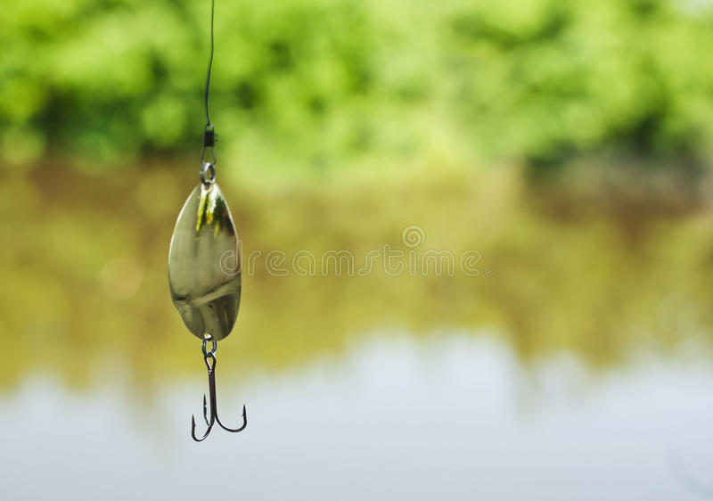 Fishing lure. Metal fishing spoon lure over freshwater river background royalty free stock images