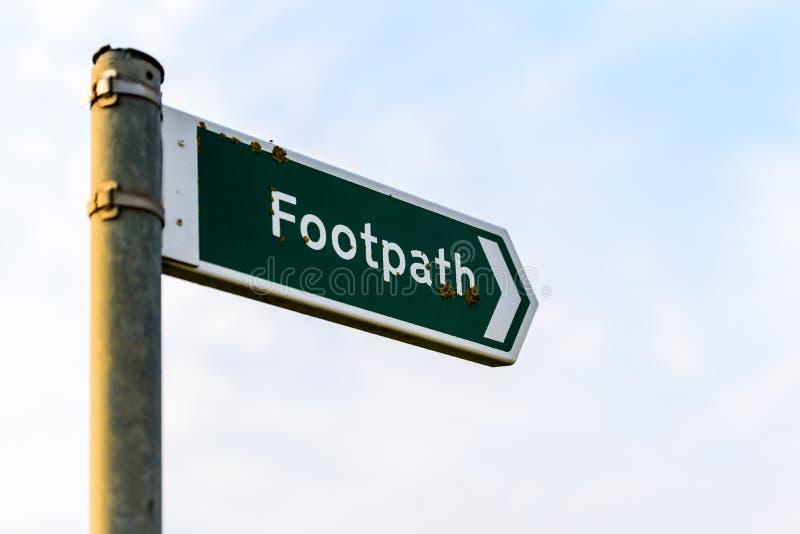 Metal footpath sign over sky background in het vk stock fotografie