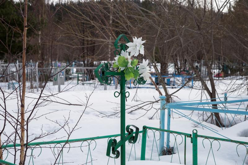 A metal forged cross with artificial flowers, on an old village cemetery. royalty free stock photography