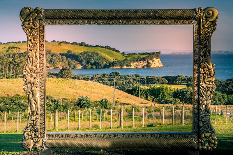 Metal frame opening to New Zealand iconic landscape - lush green hills and cliff over blue sea. Shakespear regional Park, Auckland royalty free stock images