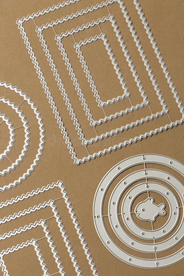 Metal frames for die cutting at work with paper for scrapbook. In town paper kraft royalty free stock image