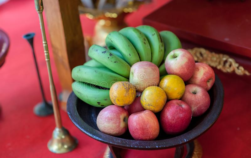 Metal fruit bowl on a wooden surface. Close. Bananas, oranges and apples. Mix of fresh apple,banana,orange, in a basket. An assortment of fresh fruits in royalty free stock photo