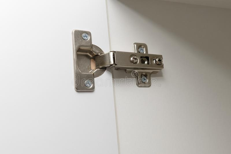 Metal furniture hinge mounted on the door of cabinet. Metal furniture hinge mounted on the door of a white cabinet stock photography