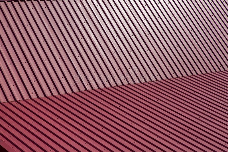 The metal gable roof covering. Red color, close-up texture span-roof stock photography