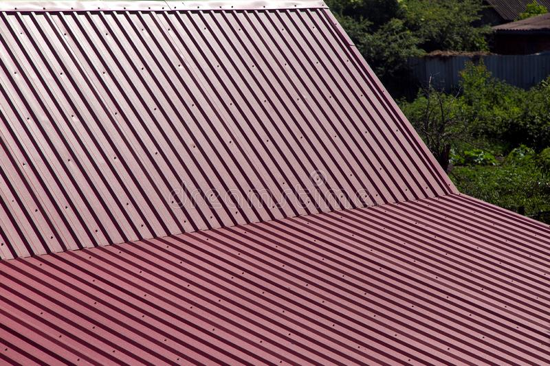 The metal gable roof covering. Gable roof top view, roof overlap with corrugated metal of red color stock images
