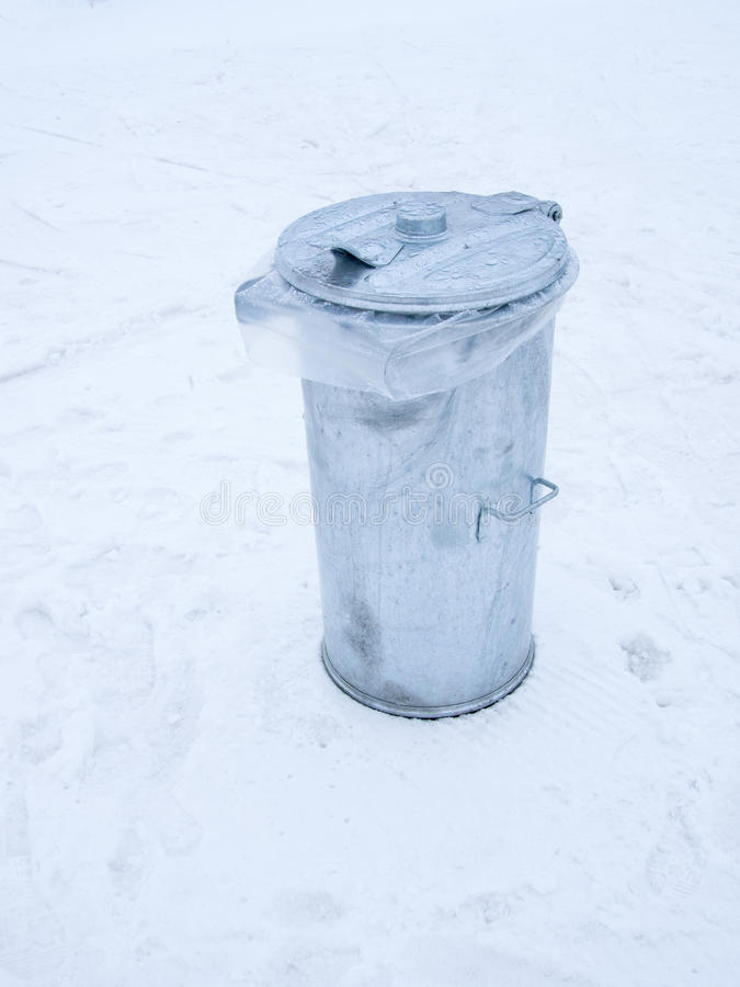 Metal garbage can with lid closed on the snow royalty free stock images