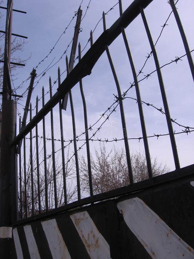 Metal gate with barbed wire closed in dangerous territory allowed royalty free stock images