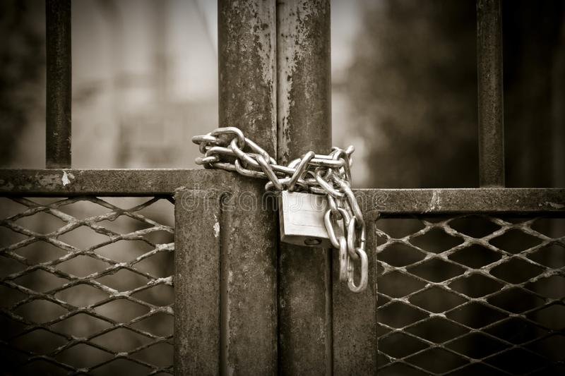 Metal gate closed with padlock - sepia toned stock photography