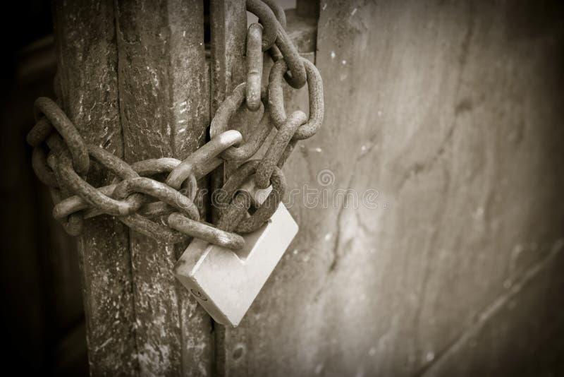 Metal gate closed with padlock - sepia toned stock photo