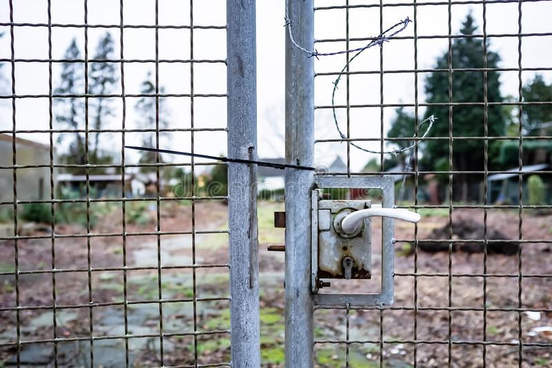 Metal gates of the welded mesh does not close on the mortise lock and hanging barbed wire protecting abandoned private property royalty free stock photo