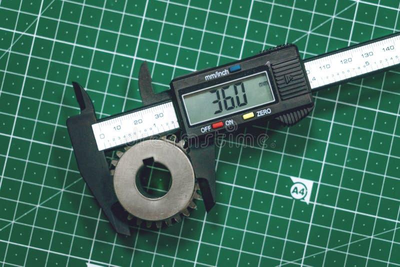 Metal gear measurement process. Measuring steel detail, gear with digital Vernier Caliper at workshop on cutting mat stock images