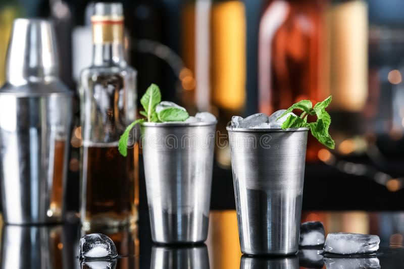 Metal glasses with tasty mint julep cocktail on bar counter stock images