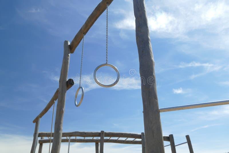 Metal gli anelli su costruzione di legno nel campo da giuoco dei bambini fotografie stock