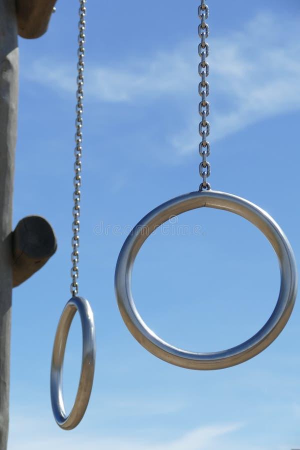 Metal gli anelli su costruzione di legno nel campo da giuoco dei bambini immagine stock
