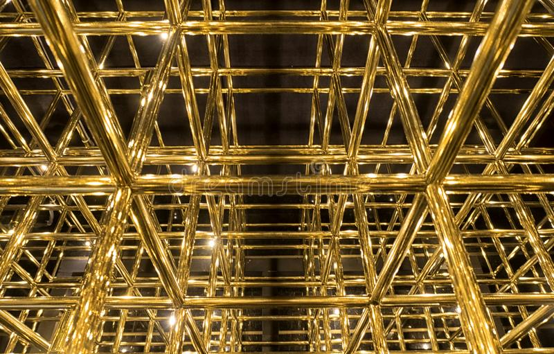 Gold grid on a black background. Metal gold grille on a black background royalty free stock images