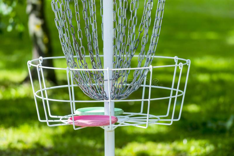 Metal golf basket in the grass and trees in the middle of the park. Basket used to play frisbee golf by throwing disc into the met royalty free stock photography