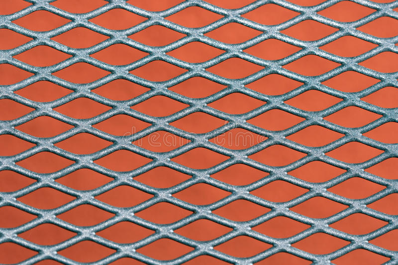 Metal grating background. Abstract metal grating against red wall background stock photography
