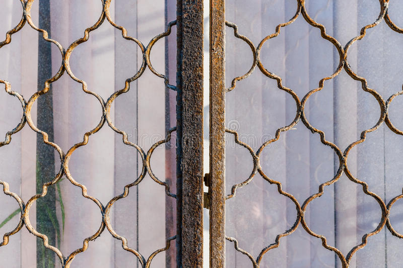 Metal grating on a closed window. Closeup view of ornately shaped rusty metal grating, lattice or reja on a window blinded with string curtains. Everything is royalty free stock image