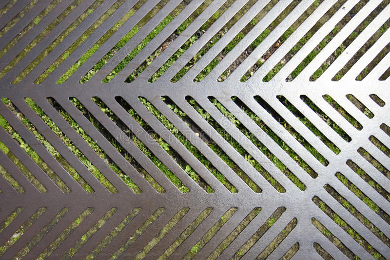 A metal grating. A fragment of a metal grating on the background of green vegetation royalty free stock photography