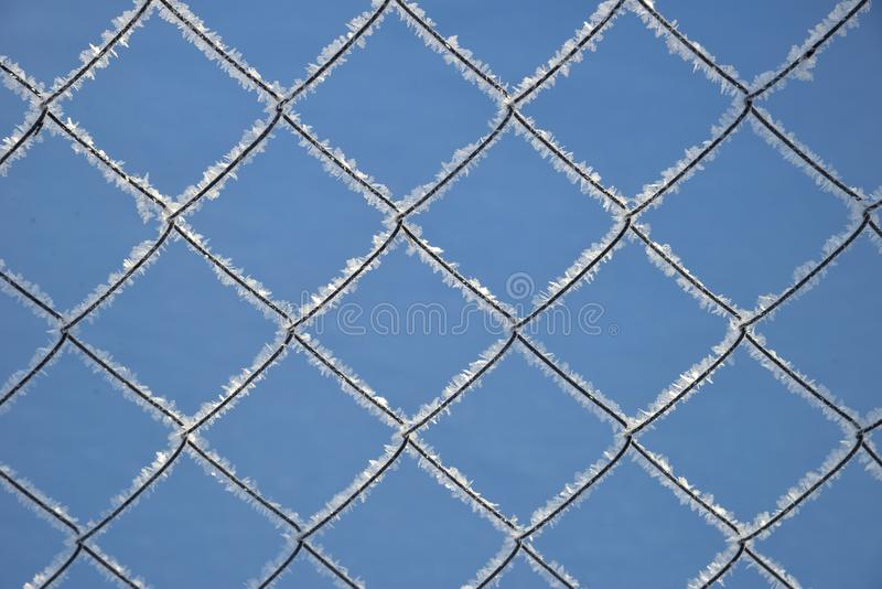 Metal grating with hoarfrost on sky background. Metal grating with hoarfrost on blue sky background stock image