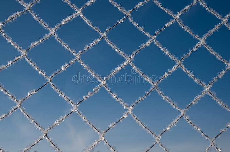 Metal grating with hoarfrost on sky background. Metal grating with hoarfrost on blue sky background royalty free stock images