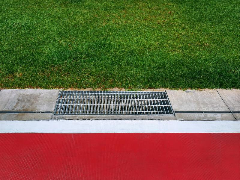 Metal Grating By Red Floor and Green Grass Field. High Angle View of Metal Grating By Red Floor and Green Grass Field royalty free stock photography