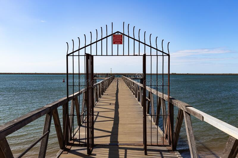 Metal grating on a wooden bridge over the ocean. On a sunny day in summer with blue sky royalty free stock image