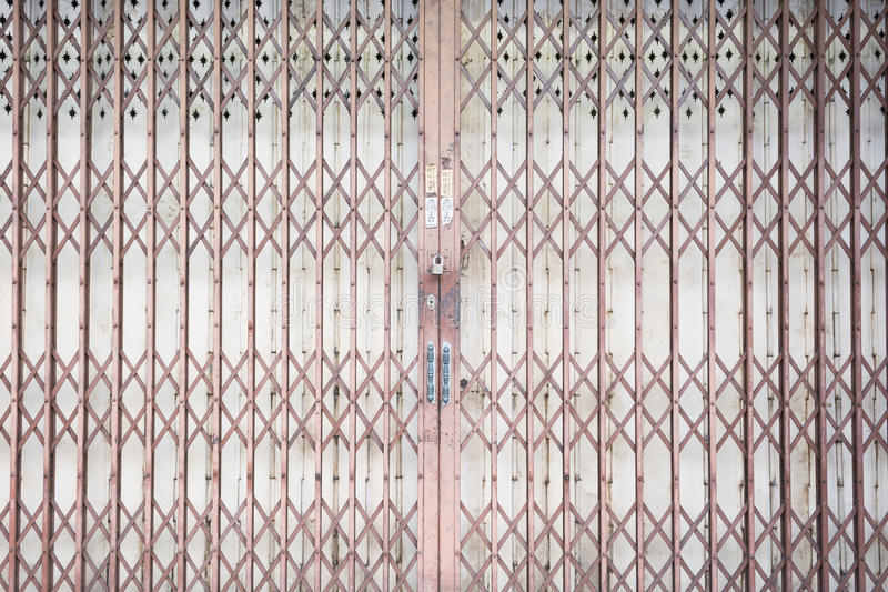 Metal grille sliding door with pad lock and aluminium handle royalty free stock photos