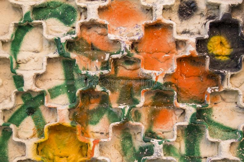 Metal grille on a white brick wall with bright yellow, orange, black and green spots and splashes of paint. rough surface texture royalty free stock photography