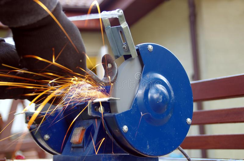 Metal grinding. Electric wheel grinding with light sparks and gleam. Industry theme background stock image