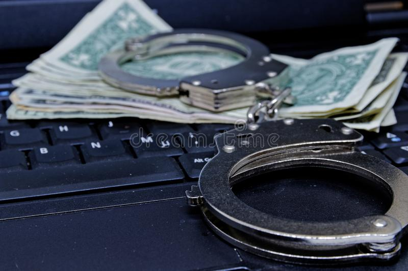 Money notes, computer keyboard and metal handcuffs royalty free stock photo