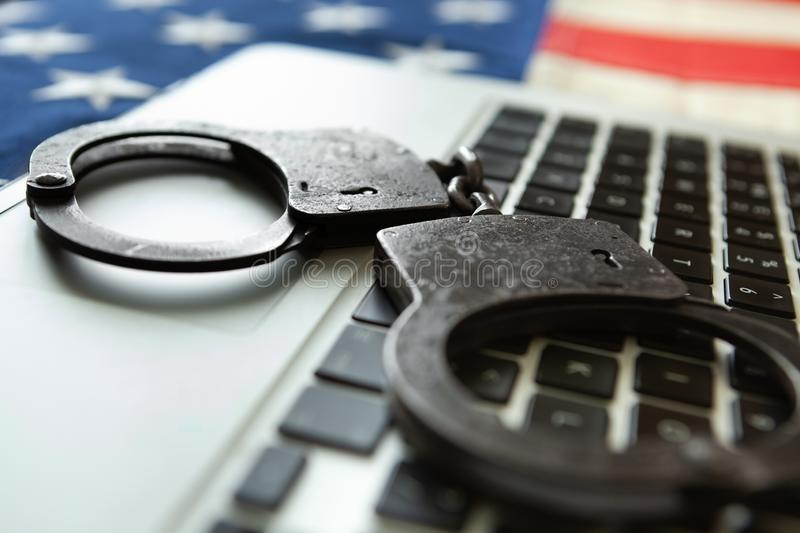 Metal handcuffs over a laptop with an old USA flag on background - close up studio shot royalty free stock image