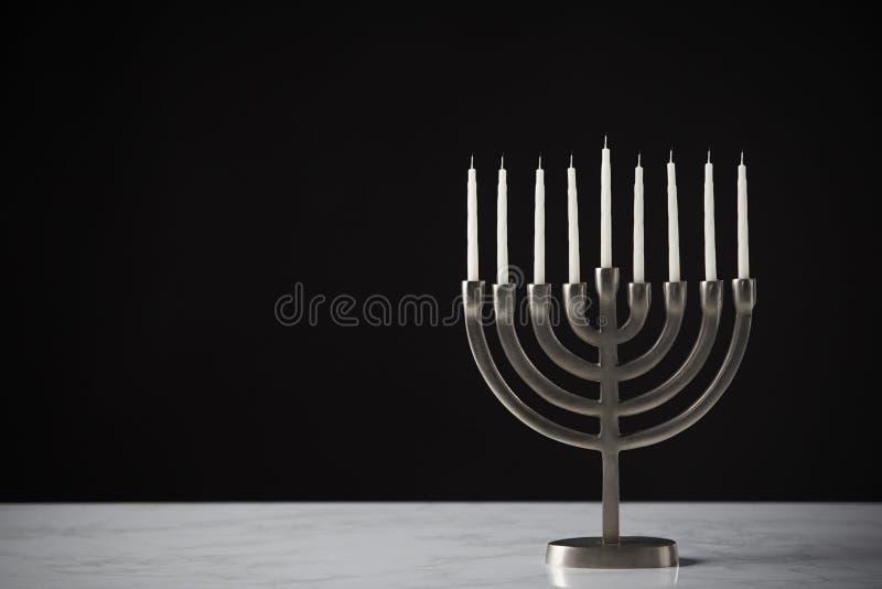 Metal Hanukkah Menorah Z Unlit świeczkami Na marmur powierzchni Przeciw Czarnemu Pracownianemu tłu zdjęcia stock