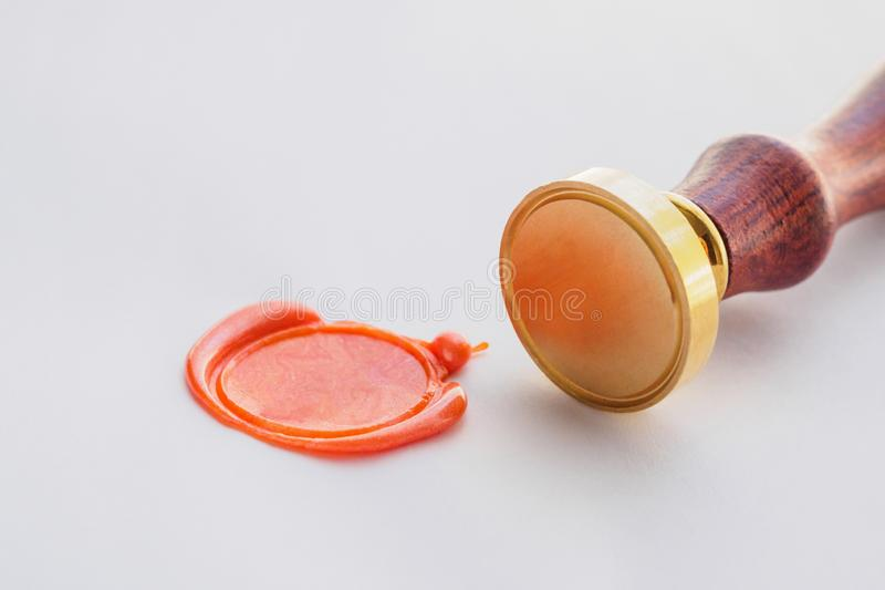 metal head stamp tool with wooden handle and wax seal on paper royalty free stock images