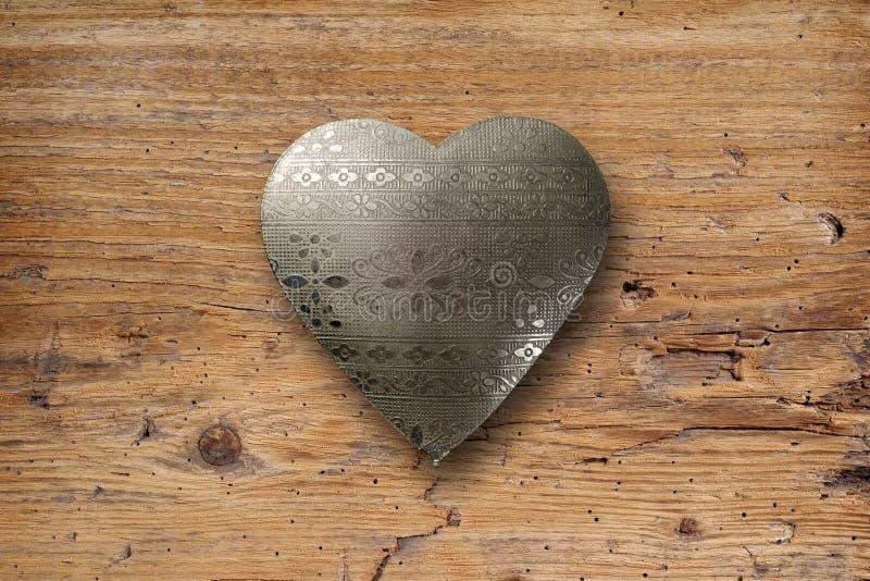Metal heart on wood stock photo