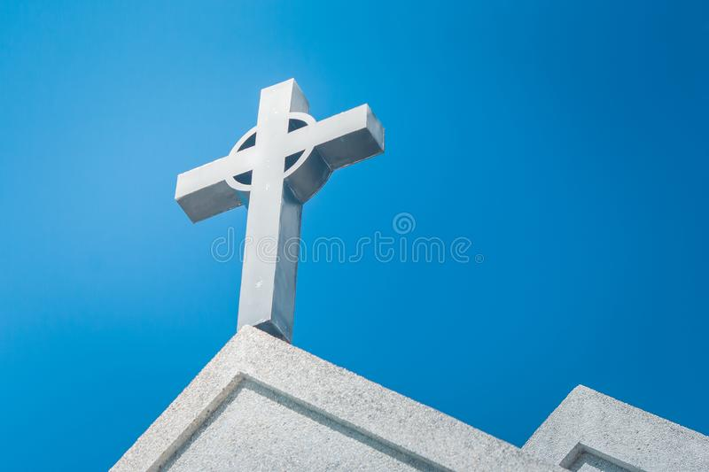 Metal holy cross or crucifix on the top of white church. Metal holy cross or crucifix on the top of white church with blue sky in the background stock image
