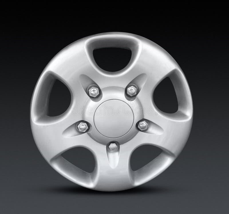 Metal hubcap or wheel trim. 3d illustration of metal alloy hubcap or wheel trim with dark studio background royalty free stock image