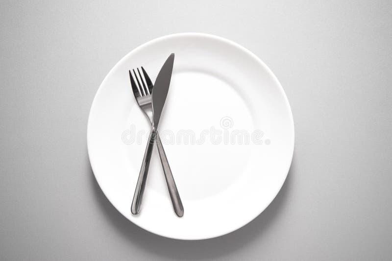 Metal il coltello e la forcella sul piatto bianco pulito per il ristorante o l'alimento fotografia stock