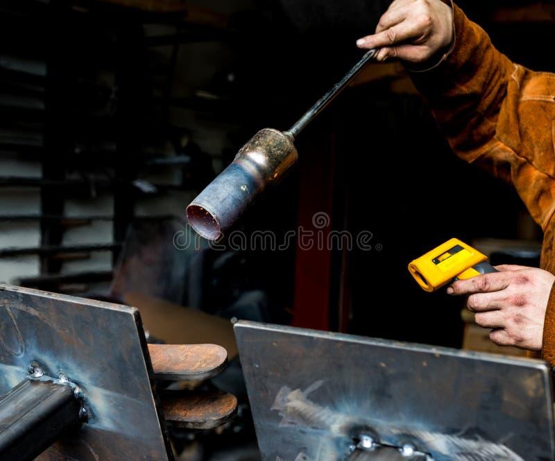 Metal il lavoratore che preriscalda le lamiere d'acciaio con una torcia del propano in preparazione della saldatura immagini stock libere da diritti
