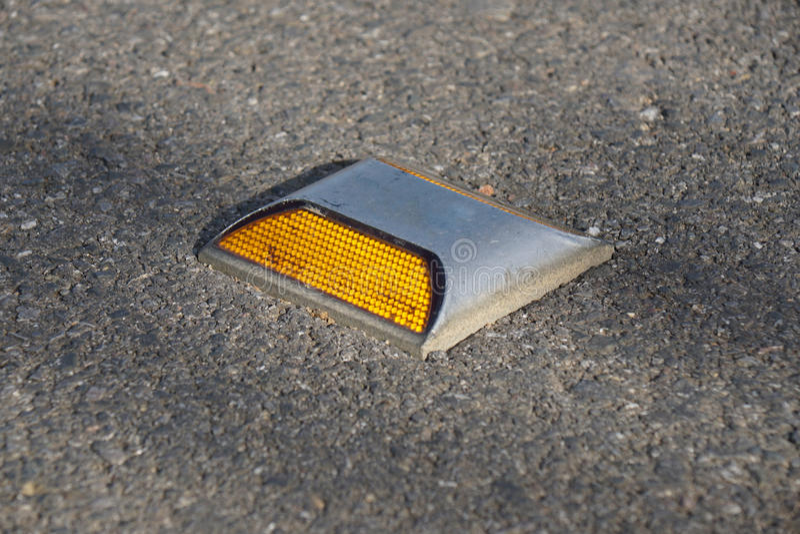 Metal il perno della strada con il riflettore giallo sulla strada asfaltata in Tailandia immagini stock