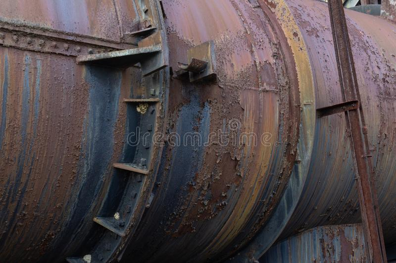 Metal industrial pipe with gaskets, rivet construction, rust patina. Horizontal aspect stock images