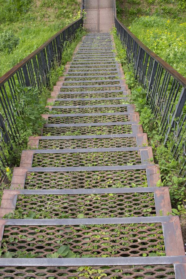Metal iron staircase leading down. Metal steps iron railings, descending from a green grassy hill stock photos