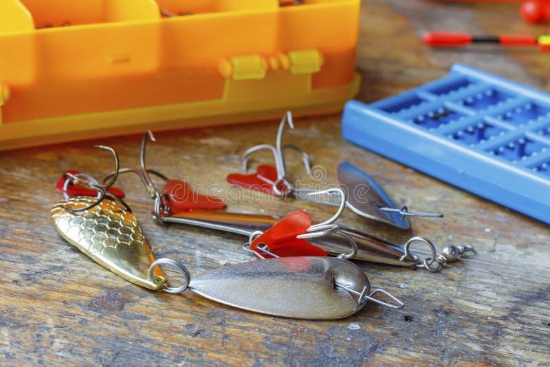 Metal iscas de pesca com acessórios em uma tabela de madeira imagens de stock