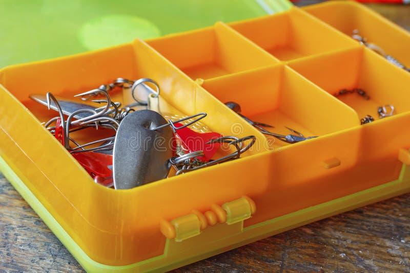 Metal iscas de pesca em um close up plástico alaranjado da caixa de armazenamento foto de stock