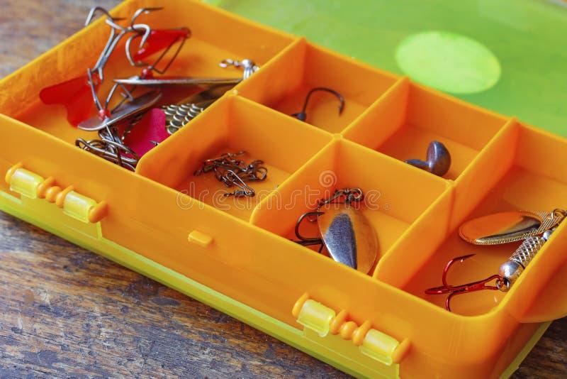 Metal iscas de pesca em um close up plástico alaranjado da caixa de armazenamento imagem de stock