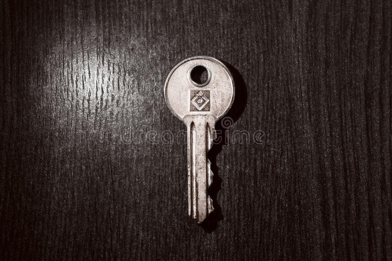Metal key hanging on a wooden door royalty free stock photo