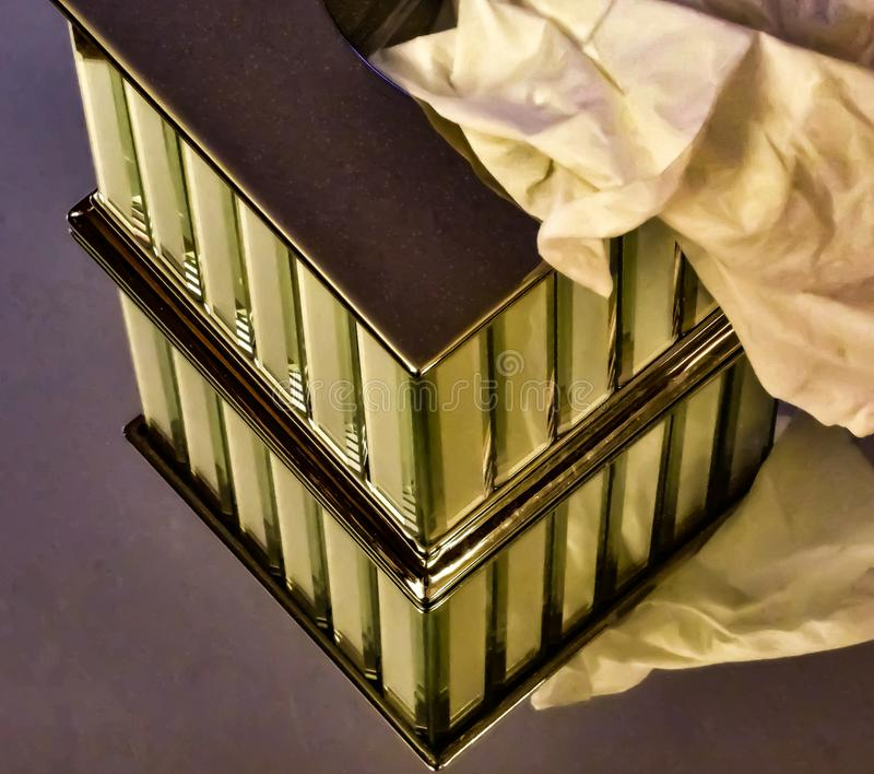 Mirrored Images Part Two. Metal Kleenex holder sitting on a mirror I laid on the ground royalty free stock photo