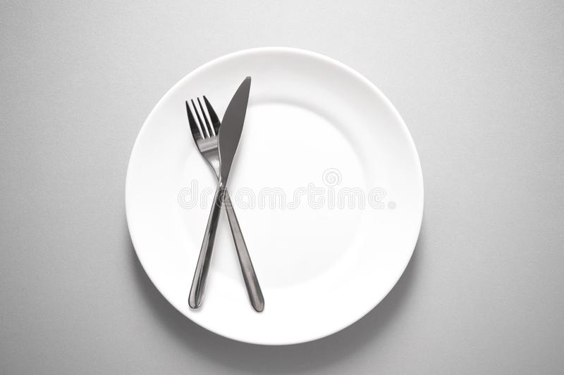 Metal knife and fork on clean white plate for restaurant or food stock photography