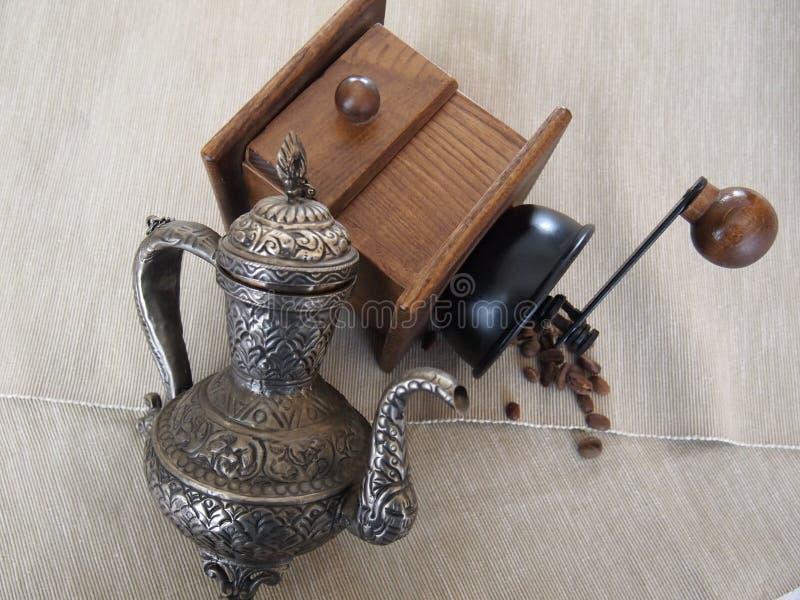 Metal la amoladora del moneda-pote y de café con los granos de café fotografía de archivo